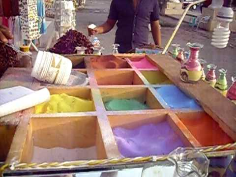 Painting with colored sand in a glass bottle