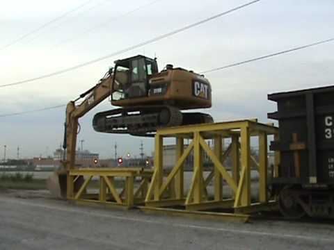 Caterpillar 319D LN excavator climbs onto a rail car to unload crushed rock