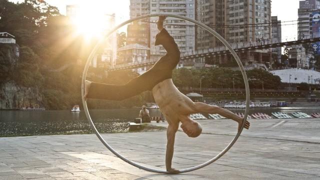 Street performer Isaac Hou rides a Cyr wheel