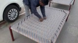 Weaving a traditional charpai bed
